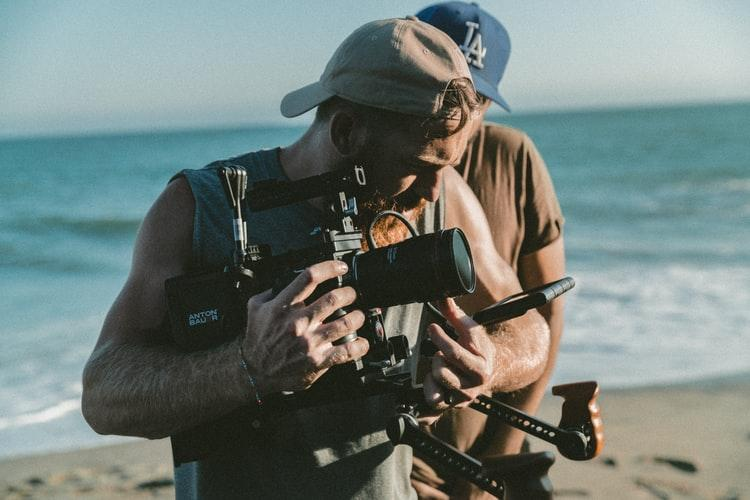 Man filming a movie on the beach